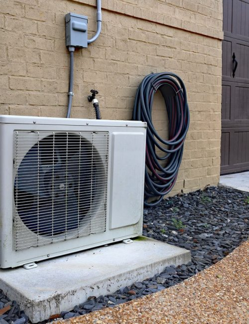 Air Conditioner mini split system next to home with brick wall Texas Air Repair