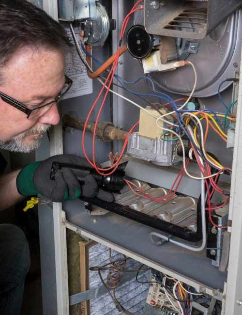 Furnace Repair San Antonio TX Technician Looking Over A Gas Furnace Texas Air Repair